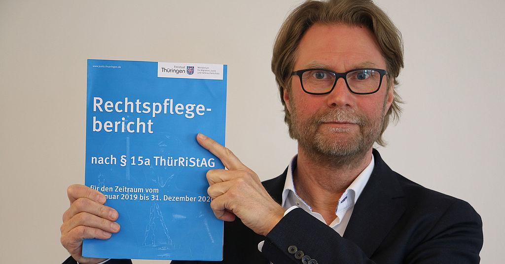 Justizminister Dirk Adams zeigt ein Exemplar des Rechtspflegeberichtes.