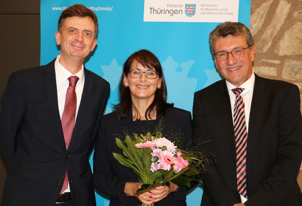Richterin Engel mit Blumenstrauß halten gesäumt von Minister und Staatssekretär