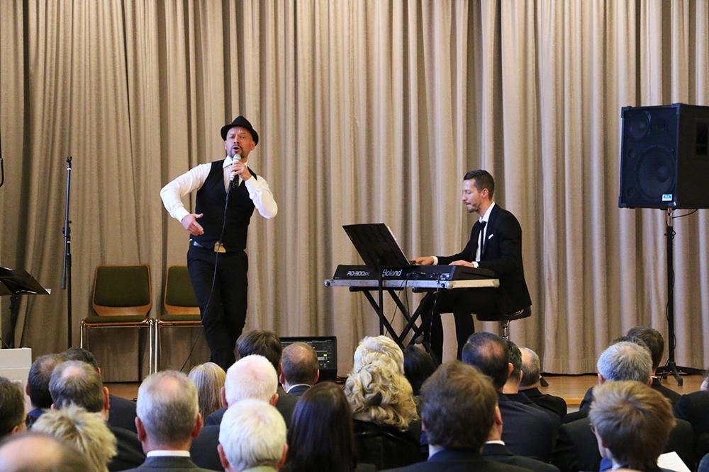 Mann mit Hut und Mikrofon stehend und singend auf Bühne, eine weitere Person begleitet am Keyboard