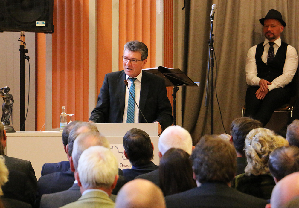 Dieter Lauinger sprechend am Rednerpult zu sitzenden mit Rücken zum Betrachter gewendeten Personen