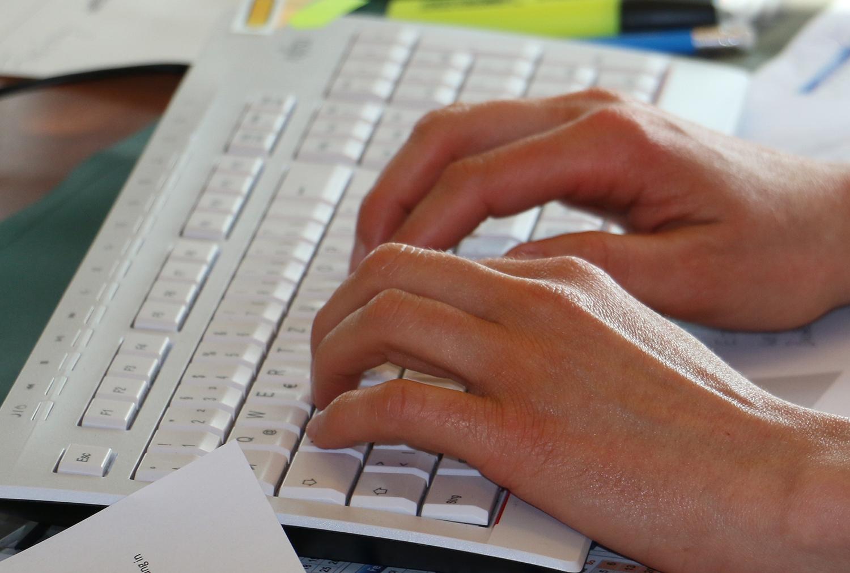 Hände schreiben mit der Tastatur einen Text