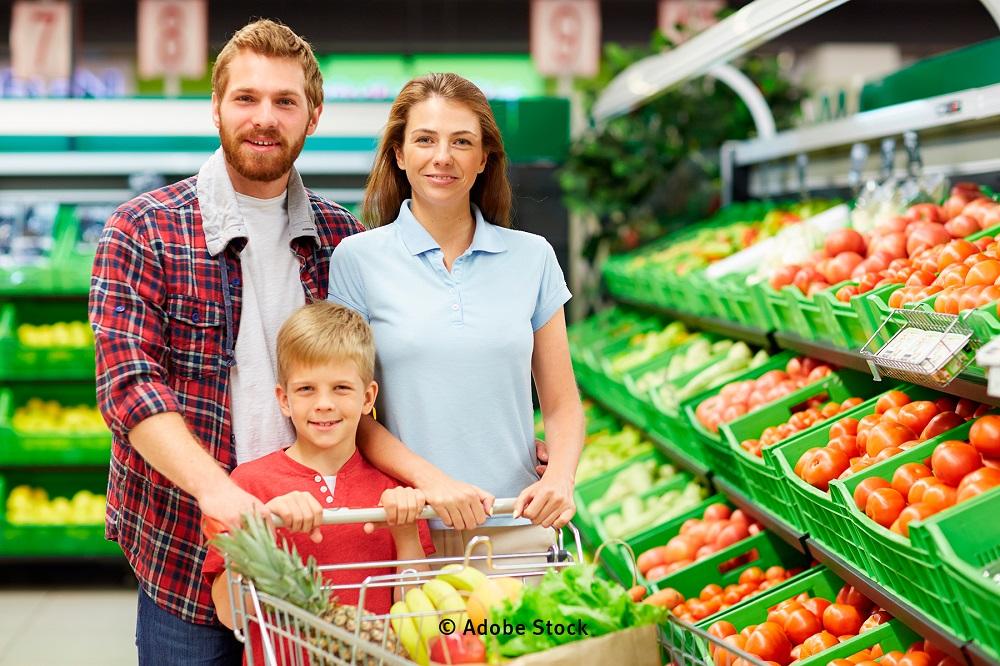 Eine Familie mit Einkaufswagen in eimem Lebensmittelgeschäft