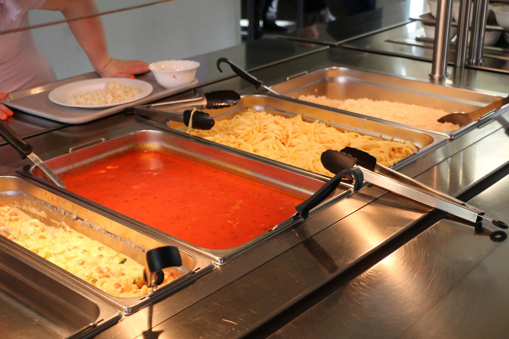 Essenausgabe in der Schule mit verschiedenen Beilagen