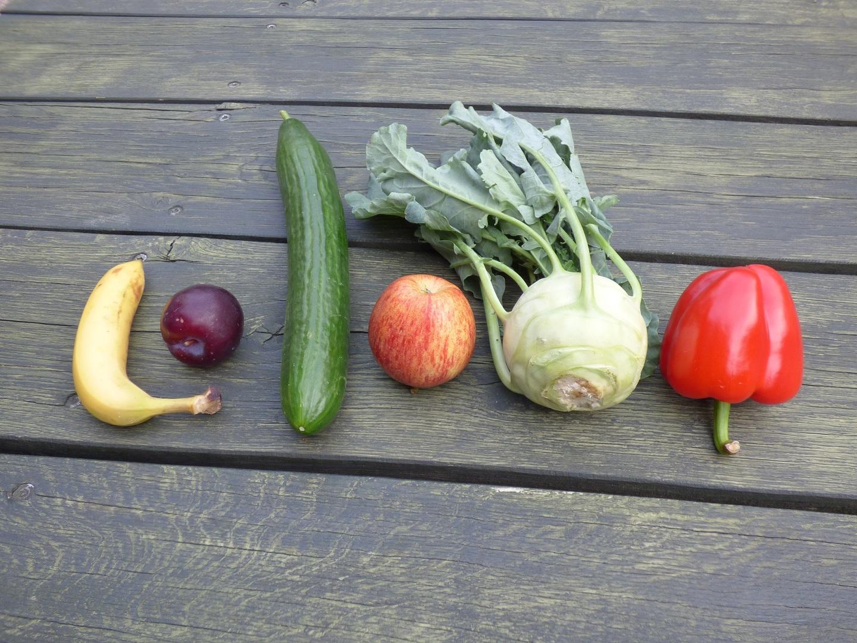 verschiedene Obst und Gemüsesorten liegen auf einen grünen Holztisch