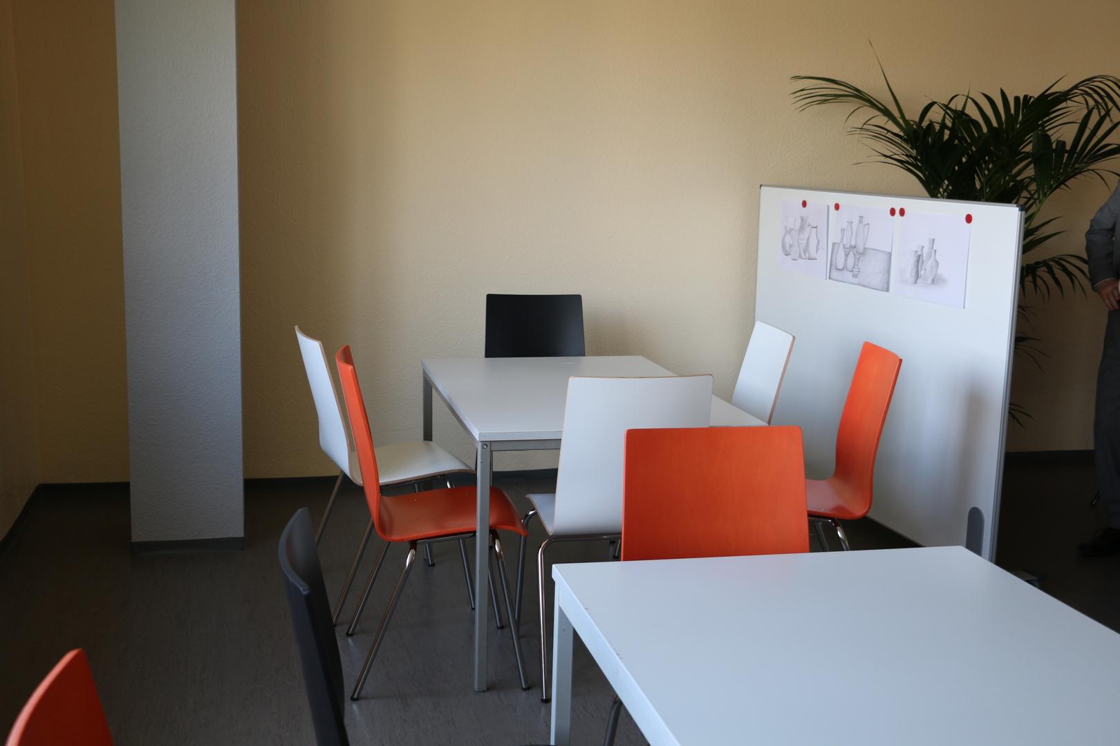 Speiseraum in einer Schule mit weißen Tischen und orangenen Stühlen und einer Ausstellungstafel