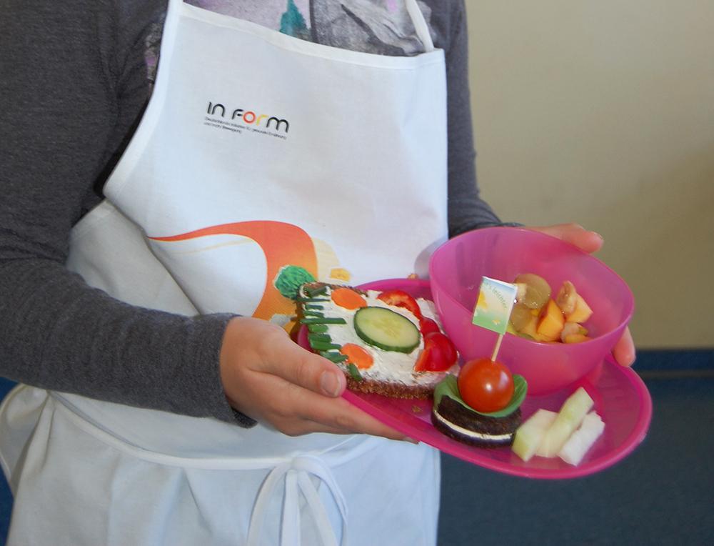 Ein Mädchen hält einen Teller mit einem Brotgesicht und verschiedenem Obst und Gemüse in der Hand.