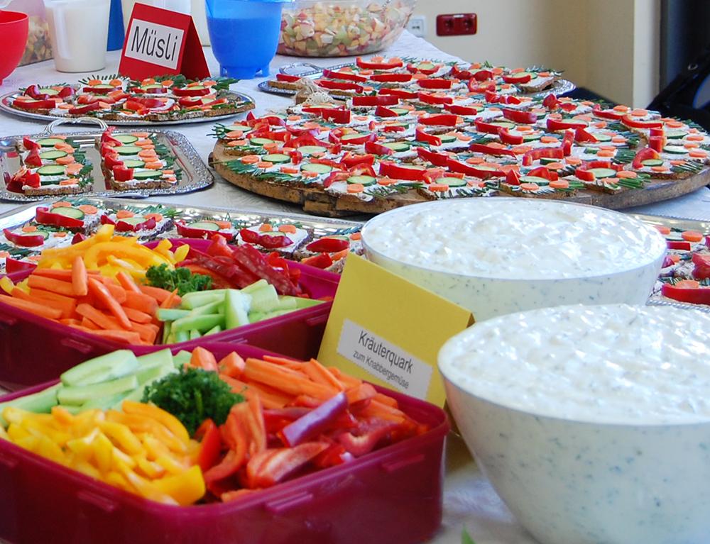 Auf einen Tisch stehen mehreren Schüsseln gefüllt mit Obst, Gemüse und Quark, Teller mit Brotgesichtern und weitere gesunde Leckereien
