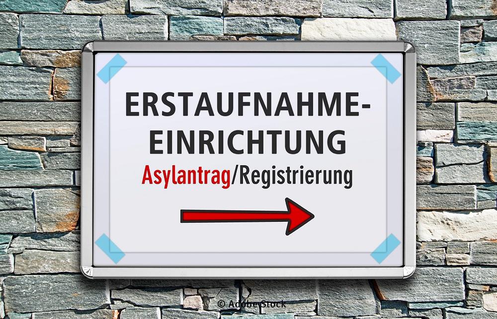 Schild mit der Aufschrift Erstaufnahmeeinrichtung und Registrierung vor einer Steinwand