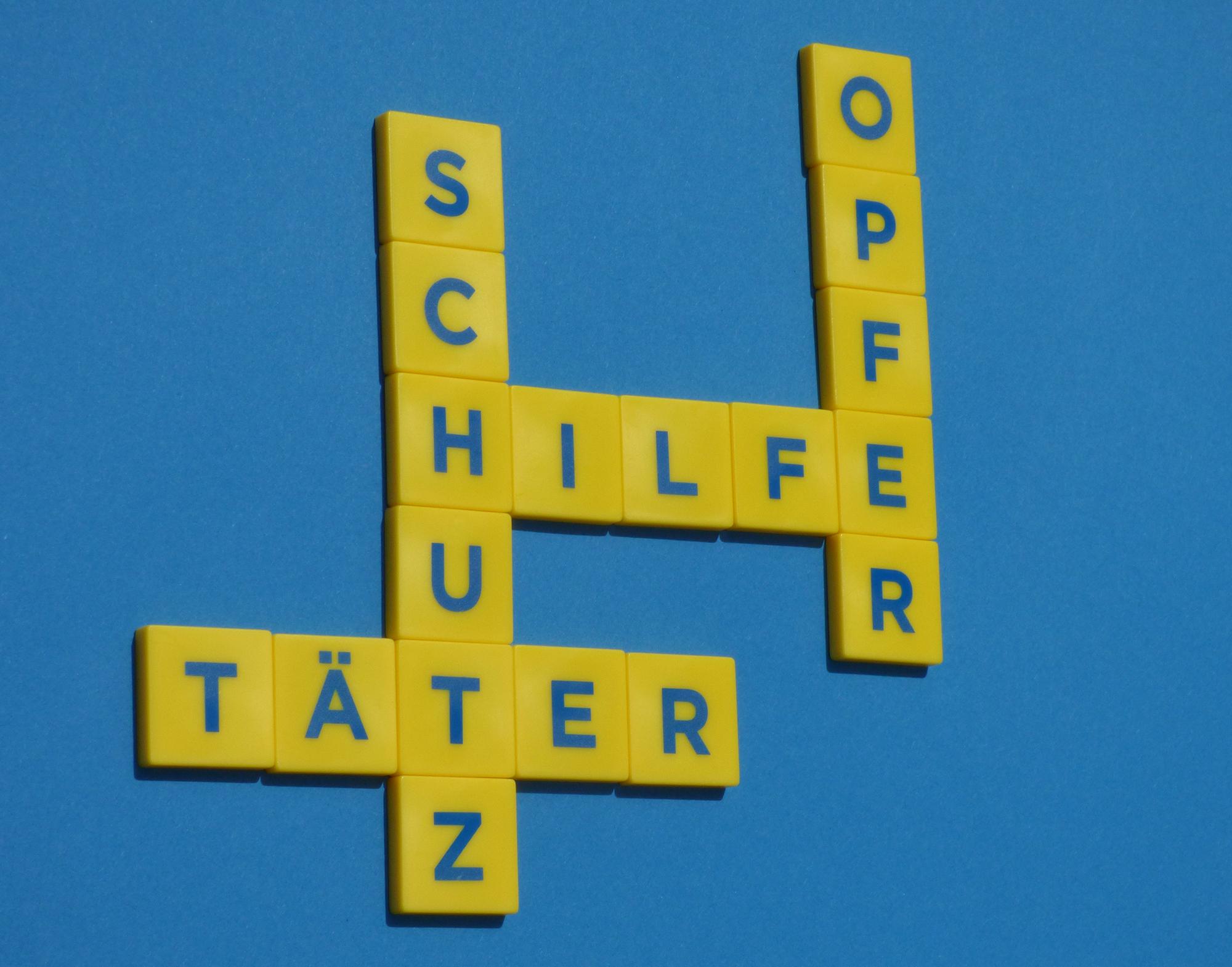 Schriftzüge Opfer Hilfe Schutz und Täter gelegt mit Buchstabensteinen