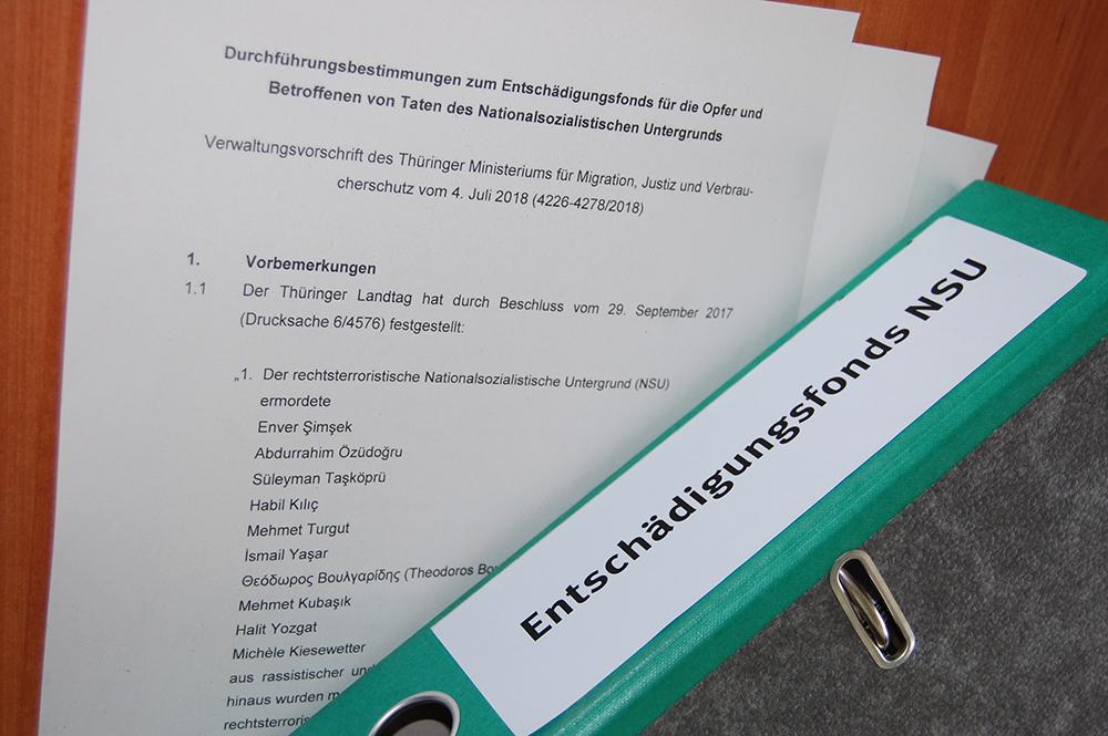 Blatt Papier mit Informationen zur NSU-Opferentschädigung und ein grüner Ordner mit Aufschrift