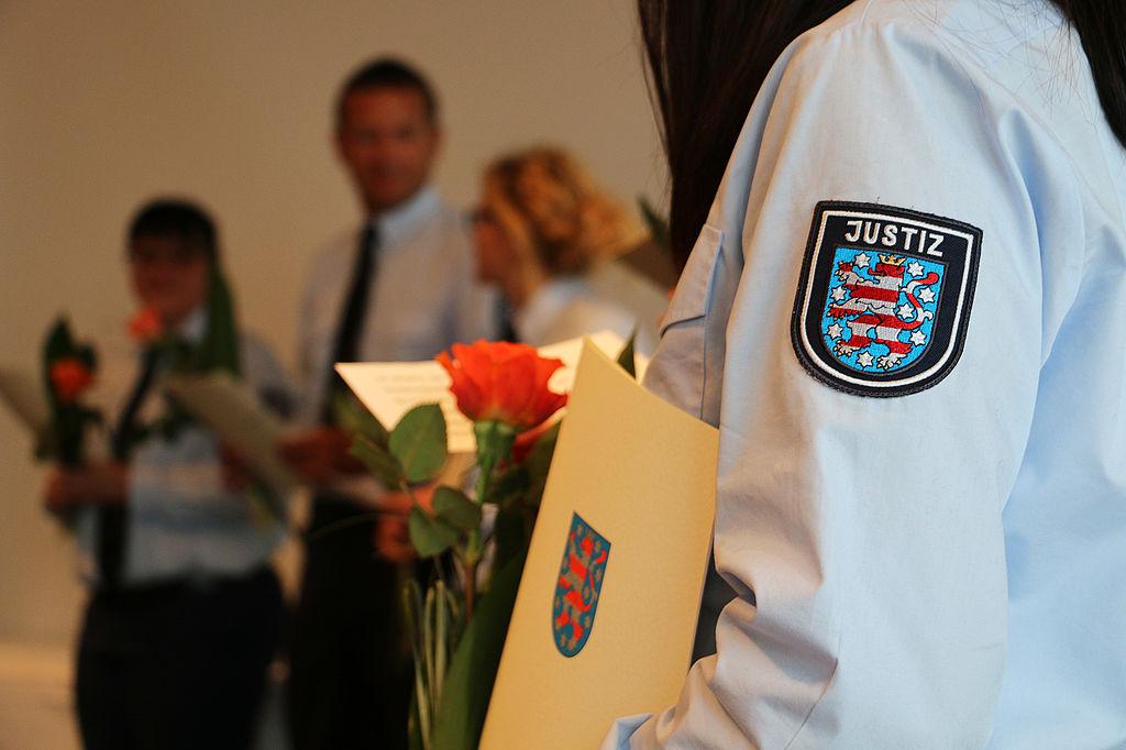 Eine Beamtin des mittleren Vollzugsdienstes hält Ihr Zeugnis und eine Blume, welches sie zum erfolgreichen Abschluss ihrer Ausbildung erhalten hat und im Hintergrund sind weitere Absolventen zu sehen.