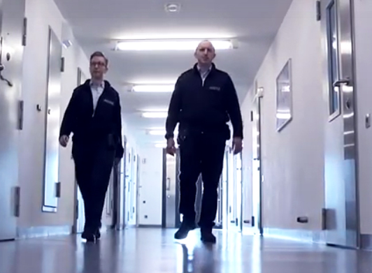 Zwei Justizvollzugsbeamte laufen über einen Gang im Hafthaus einer Justizvollzugsanstalt