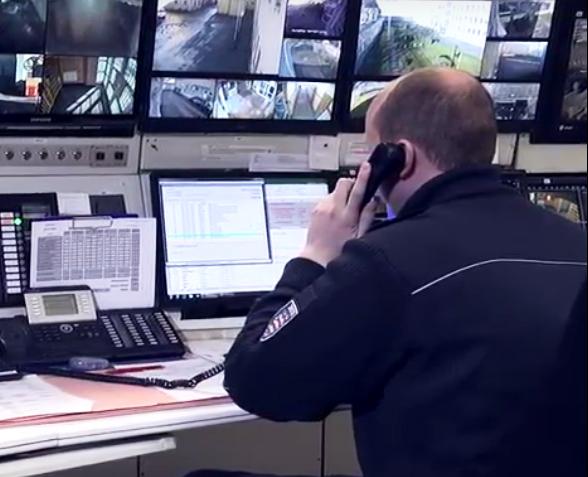 Ein Beamter des mittleren allgemeine Vollzugsdienstes sitzt in der Überwachungskanzel vor den Bildschirmen und telefoniert