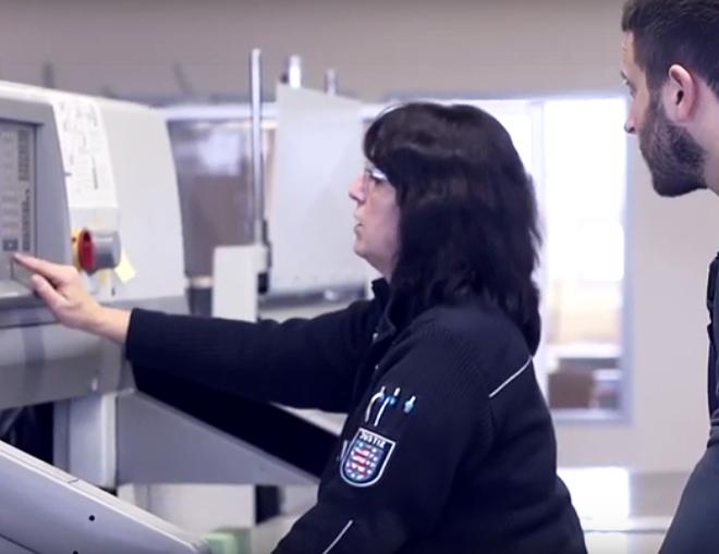 Eine Beamtin des mittleren allgemeinen Vollzugsdienstes erklärt einen Gefangenen die Maschinen in einem Arbeitsbetrieb.