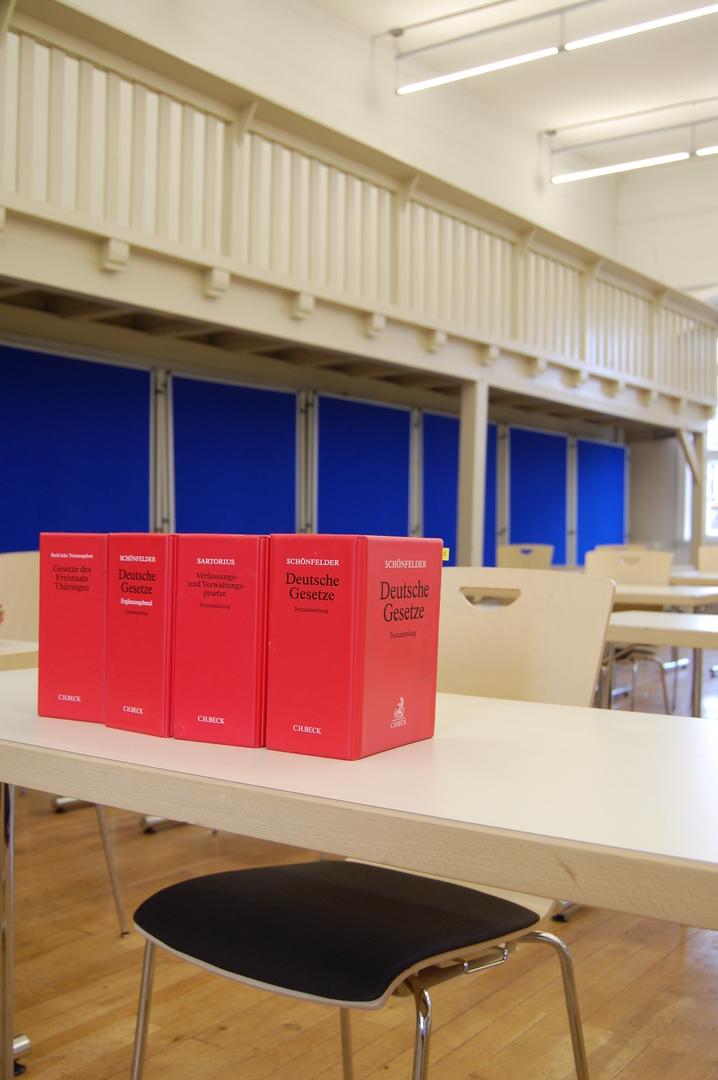 Darstellung eines fiktiven Prüfungsplatzes mit Schreibtisch, Stuhl und Gesetzestexten