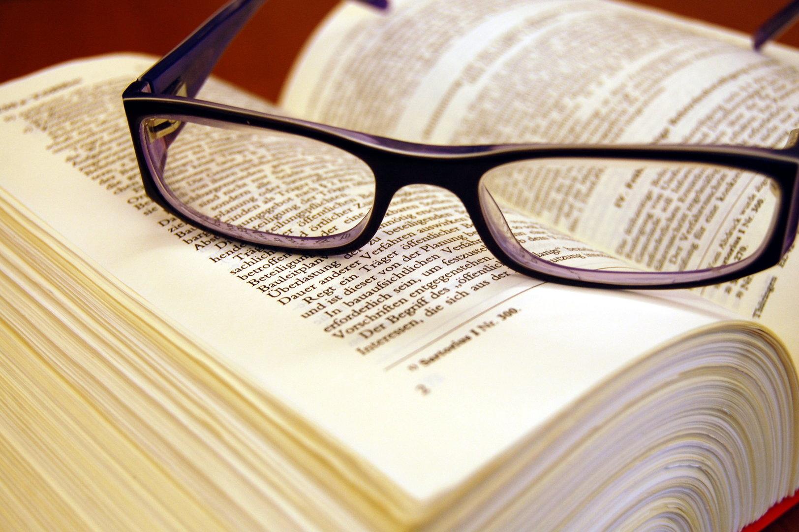aufgeschlagener Gesetzestext mit aufgelegter Brille