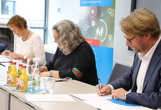 Arbeitsministerin Heike Werner, Migrationsminister Dirk Adams und Sabine Wosche, Geschäftsführerin der LEG, sitzen an einem Tisch nebeneinander und unterzeichnen die Kooperationsvereinbarung zur Fachkräftegewinnung aus dem Ausland.