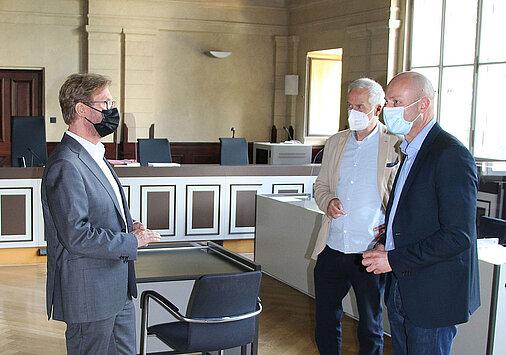 Justizminister Dirk Adams und der Direktror des Amtsgerichts Gotha, Peter Stolte unterhalten sich im Sitzungssaal des AG Gotha über die aktuelle Situation.