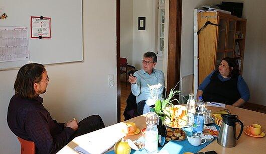 Minister Lauinger sitzend mit zwei Personen im Gespräch