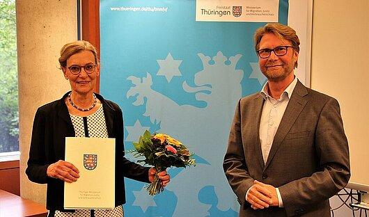 Astrid Baumann, die neue Präsidentin des Thüringer Oberlandesgerichts und Justizminister Dirk Adams vor einem Rollup des Thüringer Ministeriums für Migration, Justiz und Verbraucherschutz