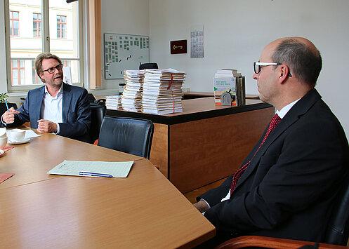 Justizminister Dirk Adams sitzt zusammen mit dem Vizepräsidenten des Landgerichts Gera, Dr. Götz Herrmann am Tisch und unterhält sich.