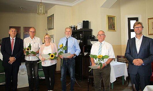 Justizminister Dirk Adams (rechts) und der Vorsitzende Richter am Landgericht Meiningen Joachim Raithel (links) danken den Ehrenamtlichen für Ihr Engagement.