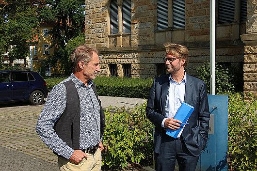 Der Präsident Gunnar Skerhut und Justizminister Dirk Adams stehen vor dem Thüringer Finanzgericht und unterhalten sich. Finanzgerichts in Gotha