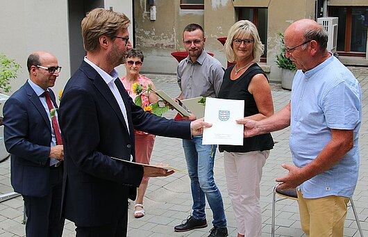 Justizminister Dirk Adamsk und der Vizepräsident des Landgerichts Gera, Dr. Götz Herrmann übergeben den Ehrenamtlichen die Urkunden und Präsente.