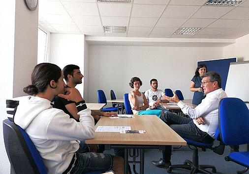 Minister Lauinger sitzend mit 2 männlichen Personen im Gespräch und 3 weitere anwesende Personen
