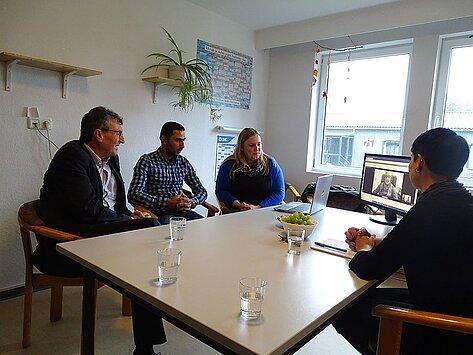 Minister Lauinger verfolgt mit 3 weiteren Personen am Tisch sitzend die Möglichkeit des Videodolmetschens im PC