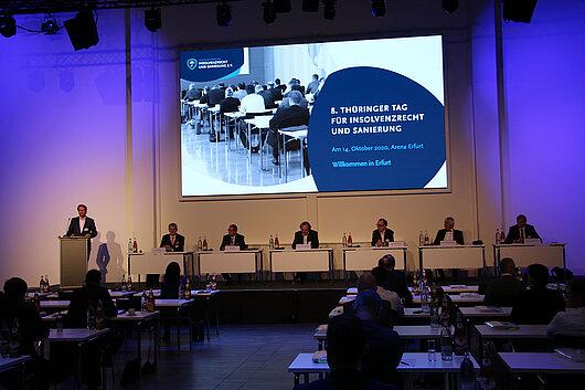 Justizminister Dirk Adams steht am Rednerpult beim Thüringer Tag für Insolvenzrecht und Sanierung und hält ein Grußwort.